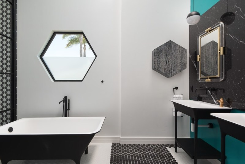 A Zucchetti Kos Italian imported tub serves as an anchor piece in the master bath. Zucchetti vanities and fixtures along with creative color-block Hexagon pattern floor tiles, Flos String Lights designed by Michael Anastassiades, and a custom hex Fleetwood window present a clean and streamlined feel and the ultimate of bespoke design expression.