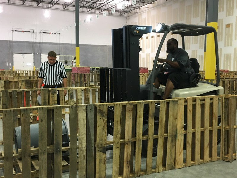 "Top Gun competitor navigates the ""pallet wall"" obstacle as the referee observes. (PRNewsfoto/GEODIS)"