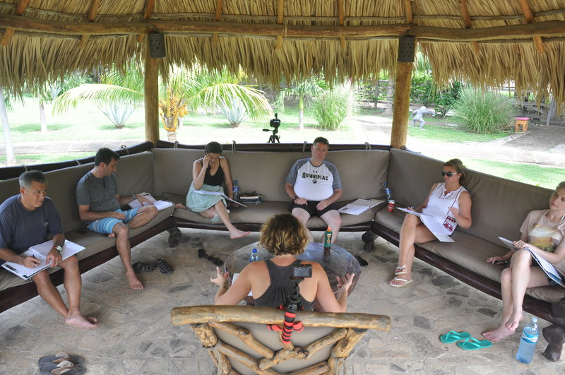 LeaderSurf participants engaging in an authentic conversation about a participants business challenge. A tiki hut makes for the right climate for learning.