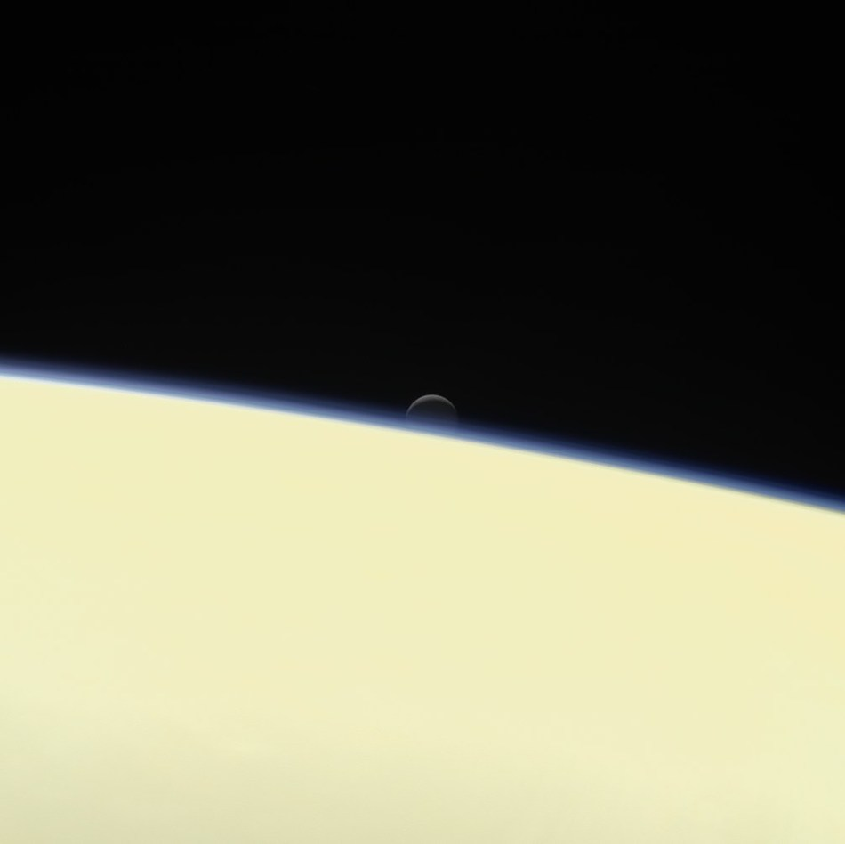 Saturn's active, ocean-bearing moon Enceladus sinks behind the giant planet in a farewell portrait from NASA's Cassini spacecraft. This view of Enceladus was taken by NASA's Cassini spacecraft on Sept. 13, 2017. It is among the last images Cassini sent back. Credit: NASA