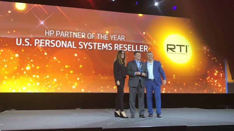 Kevin Heiss of RTI is presented with the prestigious HP Partner of the Year award from HP senior executives. (L to R) Stephanie Dismore, HP V.P. and general manager – Americas Channel; Kevin Heiss, Riverside Technologies, Inc.; Christoph Schell, HP President Americas.