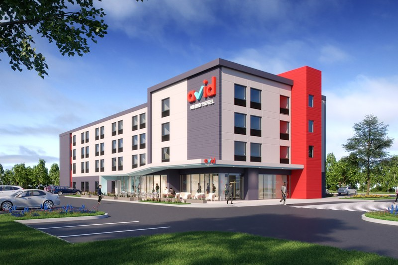 The modern exterior design of avid hotels includes an open and airy retail-like entry, a canopy and uses the stairwell as an eye catching red architectural feature.