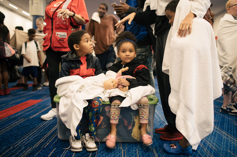 Dayvon Williams, 5, Zariah Williams, 4, wait to check in at the temporary shelter at the George R. Brown Convention Center in downtown Houston. Shown with donated Standard Textile towels. (c) Alyssa Schukar