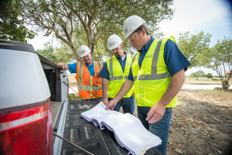 Southwest Gulf Railroad Project Manager Bart Chevreaux (center) and Vice President Erik Remmert (right) review construction plans for The Medina Line.