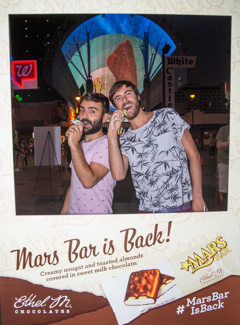 "Visitors show off their best ""Mars Bar face"" while enjoying the newly relaunched Mars Bar at Fremont Street Experience.  The world's largest digital Mars Bar was also displayed under the Fremont Street Experience canopy."