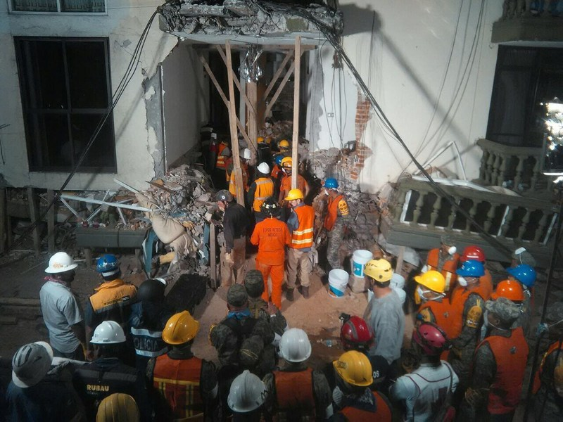 Rescue workers stand by to help at Enrique Rebsamen School, waiting for word about Paulina Gomez, one of the children trapped under the rubble.