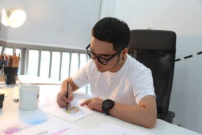 Le styliste chinois Big-King esquisse un modèle d'inspiration GuangYuYuan pour ses débuts à la Semaine de la mode à Paris