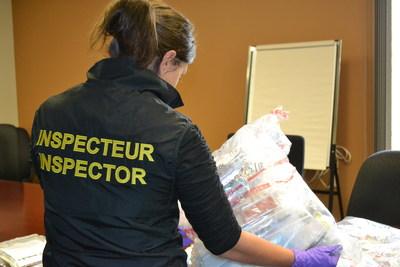 Une agente de Santé Canada inspecte des produits de santé soupçonnés d'être contrefaits et illicites qui ont été saisis pendant l'Opération Pangea X, une offensive mondiale ayant eu lieu du 12 au 19 septembre 2017. (Groupe CNW/Santé Canada)