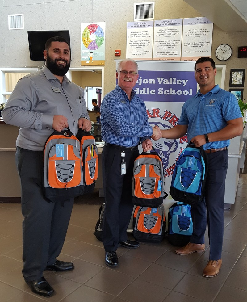 Cajon Valley Middle School Principal Justin Goodrich (right) accepts North Island Credit Union backpacks for his students from North Island Vice President & Senior Branch Manager Kirk Gentry (middle) and North Island FSR Vincent Kiti (left).