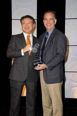 Executive Vice President of American Honda Automotive Operations, Masayuki Igarashi, presents Craig Cooke, CEO of Rhythm, with American Honda's Premier Partner Award.