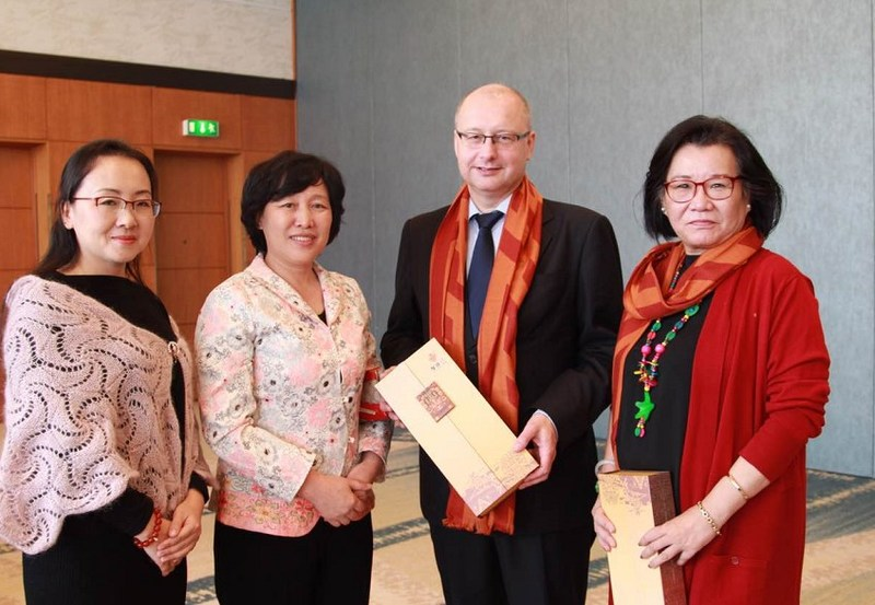 Fu Junli, Honorary President of Sanya People's Association for Friendship with Foreign Countries, giving Sanya-themed gifts to Heidi Wang, a member of the Copenhagen City Council, and Jasper Schou, an official from the Copenhagen municipal government, at The Sanya Celebration promotional meeting