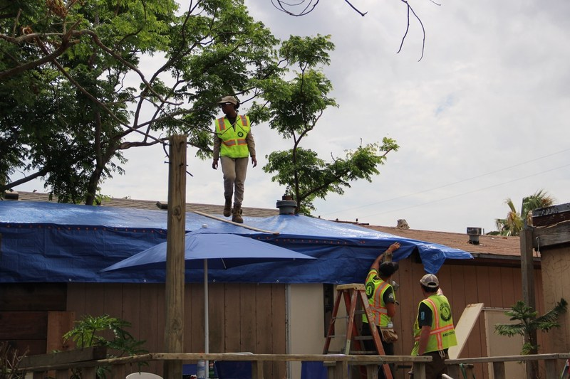 AmeriCorps members with the AmeriCorps Disaster Response Team responding to Hurricane Harvey in Texas assist a homeowner with temporary roof repairs. [Corporation for National and Community Service Photo]