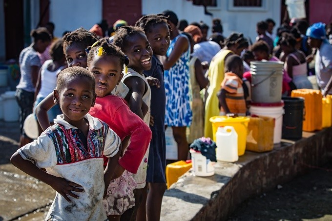 In Haiti, a month after hurricane Matthew, communities gather at a water distribution point. November 2016. © UNICEF/UN047345/Bradley (CNW Group/UNICEF Canada)