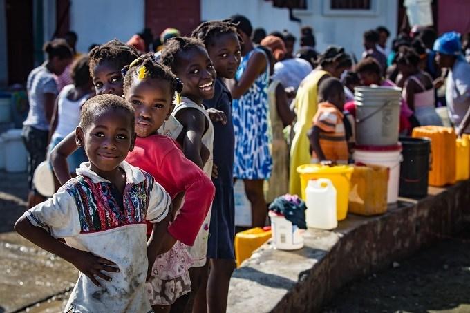 En Haïti, un mois après le passage de l'ouragan Matthew, les communautés se rassemblent à un point de distribution d'eau. Novembre 2016. © UNICEF/UN047345/Bradley (Groupe CNW/UNICEF Canada)