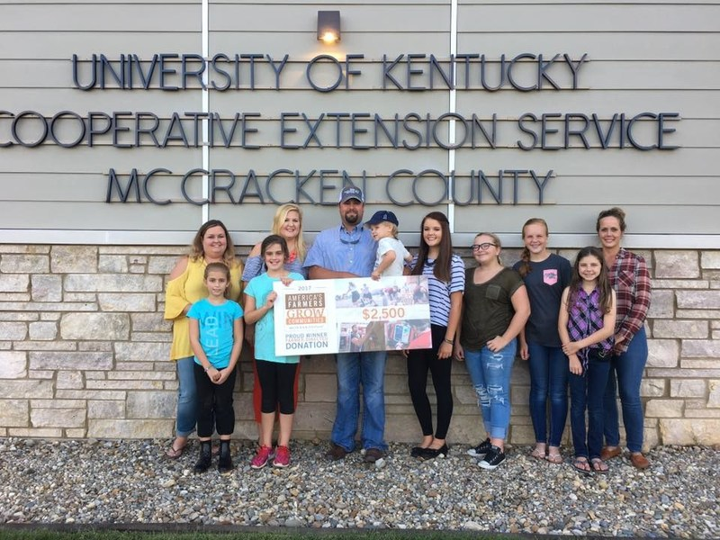 McCracken County farmer Jeremy Jordan (center) holds the check for his donation to the Carson Park 4-H Horse Club next to his family members and members of the horse club.