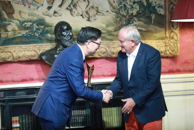 "Former French Prime Minister Jean-Pierre Raffarin presents GuangYuYuan Chairman Guo Jiaxue with an award for ""Most Influential and Innovative International Brand"" at the 2017 Select Fashion Awards"
