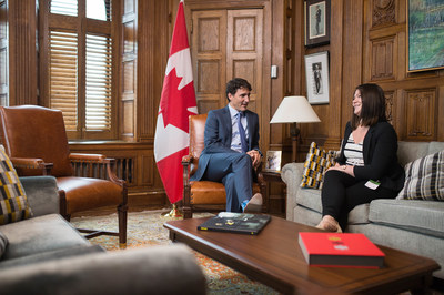 Prime Minister Justin Trudeau shares his office with Breanne Lavallée-Heckert, 23, on Oct. 5 as part of Plan International Canada's #GirlsBelongHere initiative, which celebrates girls in positions of leadership and power leading up to International Day of the Girl. (CNW Group/Plan International Canada)