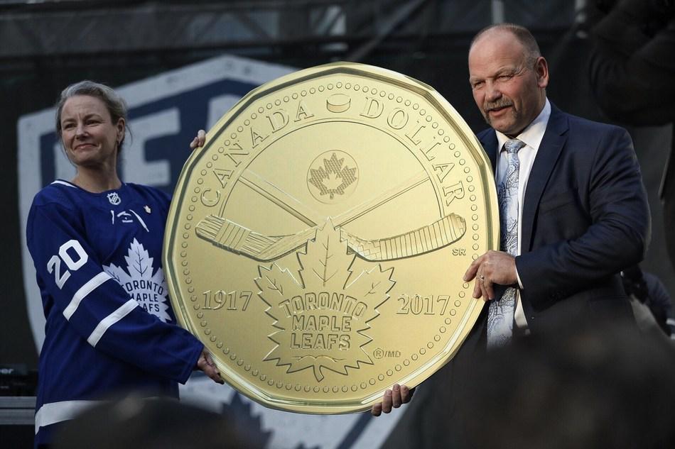 De la gauche : Sandra Hanington, présidente de la Monnaie royale canadienne et Wendel Clark, ancien joueur des Maple Leafs de Toronto et dévoilent la pièce de circulation de 1 $ soulignant le 100e anniversaire des Maple Leafs à Toronto (Maple Leafs Square, le 7 octobre 2017). (Groupe CNW/Monnaie royale canadienne)