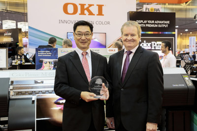 "OKI Data Americas President and CEO Kiyoshi Kurimoto accepts a 2018 Pick award for Outstanding Enhanced CMYK Eco-Solvent/Latex 54""/64"" Printer from David Sweetnam, Director of Research and Lab Services at Keypoint Intelligence Buyers Laboratory (BLI) at SGIA Expo in New Orleans, Louisiana, on Wednesday, Oct. 11, 2017."