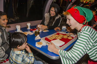This happy elf is serving cocoa and cookies on the Train to Christmas Town, in the dome car.