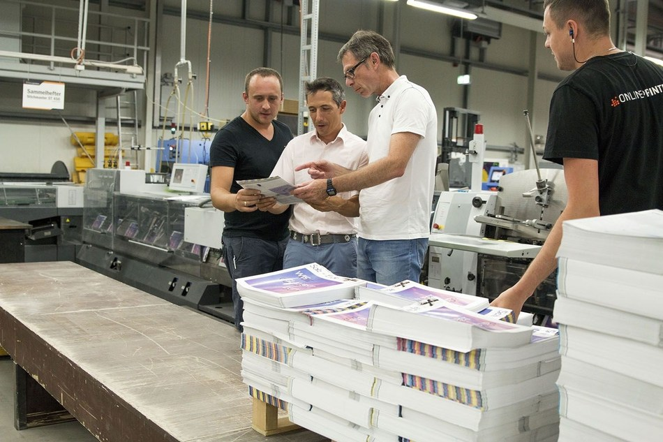 As one of the first print shops in Europe, Onlineprinters successfully certified its postpress operations. Armin Schörghofer (2nd from right), Ugra auditor, examines brochures in postpress together with co-auditor Thomas M. Schnitzler. (PRNewsfoto/Onlineprinters GmbH)