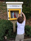 Young boy uses a Little Free Library book exchange in Minneapolis, MN