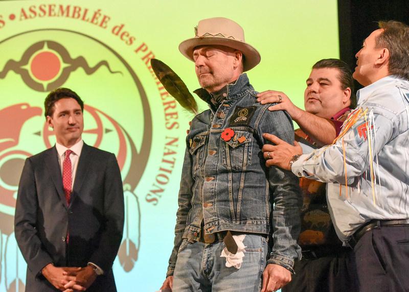 Gord Downie honoré en décembre 2016 par l'Assemblée extraordinaire des Chefs de l'Assemblée des Premières Nations, lors de la remise d'une plume d'aigle, un honneur très significatif, et de la cérémonie du nom où il s'est vu attribuer le nom de Wicapi Omani, qui signifie « Marche avec les étoiles » en Lakota. (Groupe CNW/Assemblée des Premières Nations)