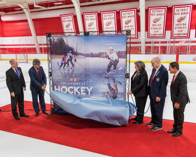 """Presentation of the souvenir sheet first day of issue special envelope at a ceremony today at Detroit's Little Caesars Arena Belfor Training Center (left to right): Master of ceremonies Paul Gross; Deepak Chopra, Canada Post President and CEO; Megan Brennan, USPS Postmaster General and CEO; Leonard """"Red"""" Kelly, member of the Hockey Hall of Fame; Dr. Murray Howe, Gordie Howe's son. Photo by Daniel Aszal, USPS (CNW Group/Canada Post)"""