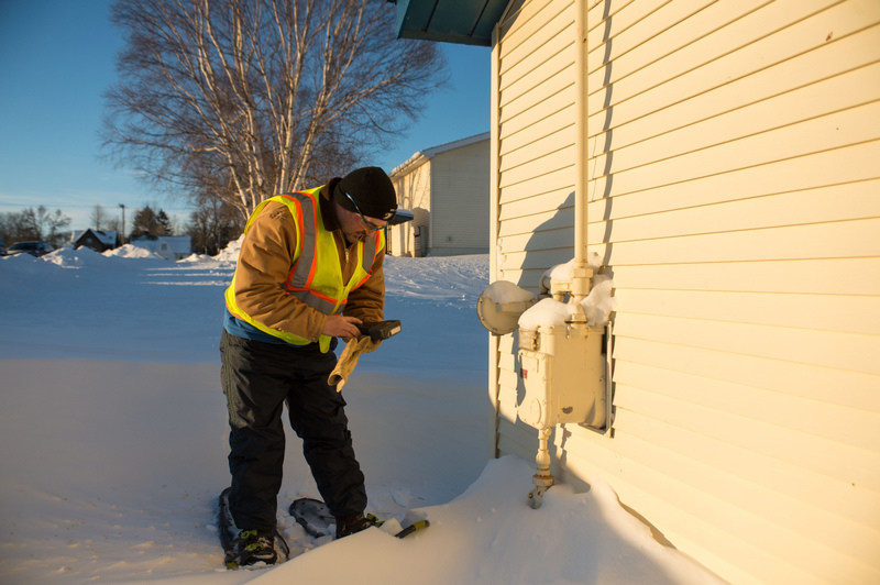 DTE Energy service tech. reads gas meter in Sault Ste. Marie, Mich.