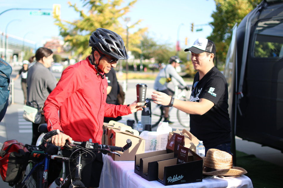 Ziwei Zhang, Developer at Traction on Demand, passes out free coffee to commuters during the 2016 Bandit Tour for Good Kick-Off. (CNW Group/Traction on Demand)