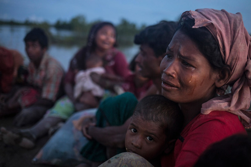 On 9 October 2017, Rohingya refugees, including women and children, cross from Myanmar into Bangladesh at Palong Khali in Cox's Bazar district. (Right) Hasina Begum, 30, weeps for the recent loss of many family members in Myanmar. © UNICEF/UN0139414/LeMoyne (CNW Group/UNICEF Canada)