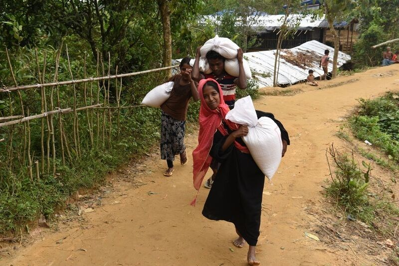 A refugee family at the camp in Cox's Bazar receiving food assistance from World Vision (CNW Group/World Vision Canada)
