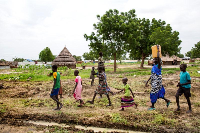 Des enfants marchent aux côtés d'Angelina, alors qu'elle rapporte un bidon d'eau potable rempli à la pompe de l'école primaire Machakos à Bentiu, au Soudan du Sud. Juillet 2017. © UNICEF/UN075394/Kealey (Groupe CNW/UNICEF Canada)