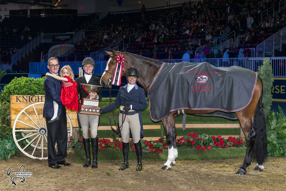 Jeff Brandmaier (left), Muffie Guthrie, and their daughter, Liza Jean, presented Erynn Ballard and Enchanted with the Lorna Jean Guthrie Challenge Trophy for the Canadian Hunter Derby Champion. Photo by Ben Radvanyi Photography (CNW Group/Royal Agricultural Winter Fair)