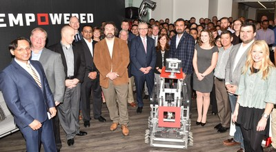 Empowered employees along with a robot created by grade school students from grades K-12 from Queen City Robotics take part in today's ribbon cutting ceremony for Empowered's new office space in Charlotte, NC.