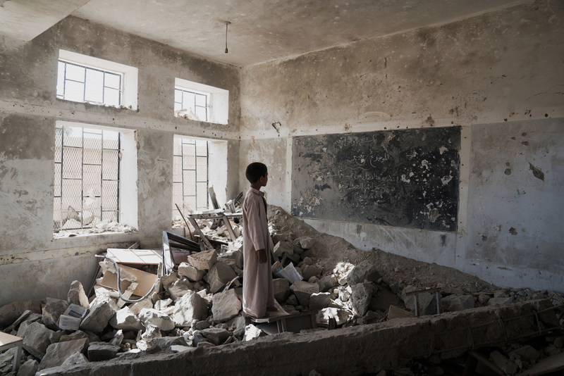 A student stands in the ruins of one of his former classrooms, which was destroyed in June 2015, at the Aal Okab school in Saada, Saada Governorate, Yemen, Monday 24 April 2017. Students now attend lessons in UNICEF tents nearby. (CNW Group/UNICEF Canada)