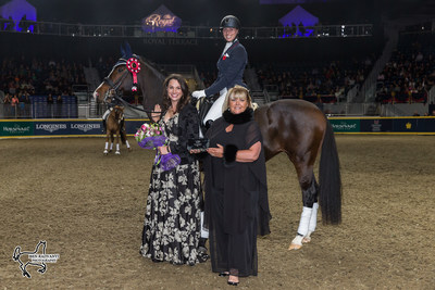 Megan Lane aboard Caravella was presented with the Butternut Ridge Trophy by Emily Hill (left) and Deborah Kinzinger Miculinic as the overall winner of the $20,000 Royal Invitational Dressage at the Royal Horse Show in Toronto, ON. Photo by Ben Radvanyi Photography (CNW Group/Royal Agricultural Winter Fair)