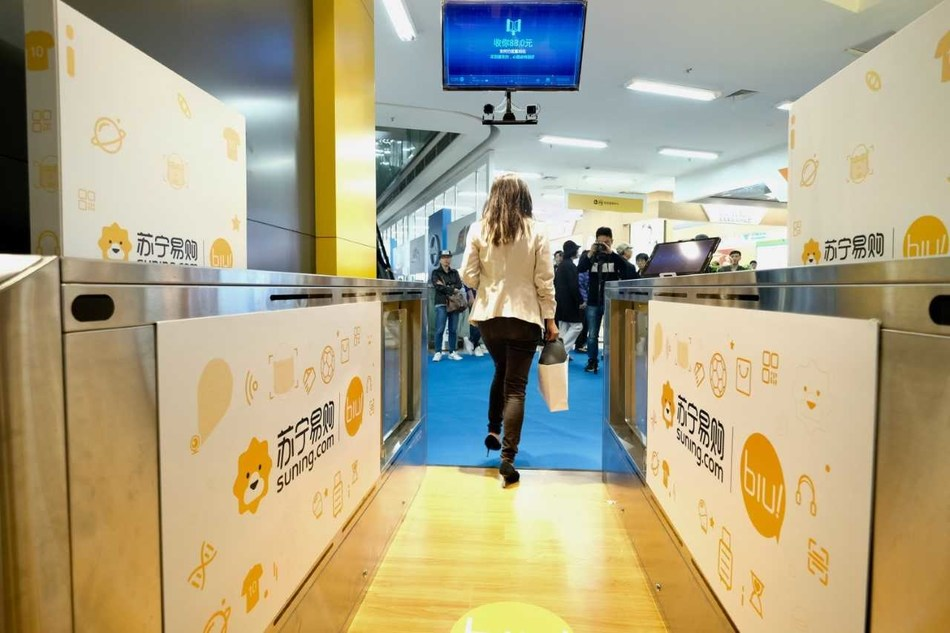 A customer walks through the self-service check-out area at the Suning unmanned store
