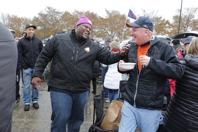 """Spice Adams, a retired professional football player, teams up with Kellogg's Raisin Bran to help tailgaters in Chicago start their day """"Sunny"""" by surprising them with a mobile game day breakfast cart, complete with milk-dispensing keg, on November 12, 2017."""