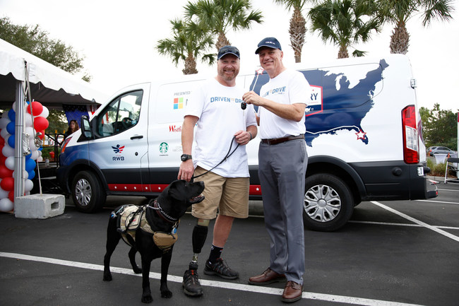 U.S. Army Veteran Major Peter Way receives the keys to his new van from TrueCar CEO Chip Perry during the closing ceremony of Team Red White & Blue's Old Glory Relay at the Westfield Brandon Mall in Tampa, Fla. on Saturday, November 11, 2017. Way won the van after entering a giveaway contest hosted by TrueCar as part of their DrivenToDrive program, which is dedicated to helping veterans regain personal freedom through driving. (Photo by Brian Blanco/Invision for TrueCar/AP Images)