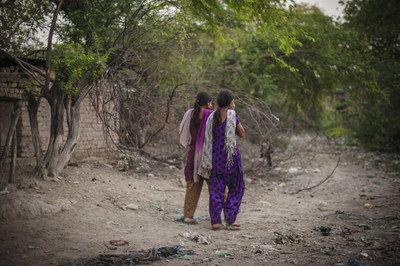 In the evening Kajal, 16, walks with her close friend and cousin Sarita, 17, (pink scarf) to the toilet in an open defacation area, Nihura Basti, Kanpur, India. WaterAid/ Poulomi Basu (CNW Group/WaterAid Canada)