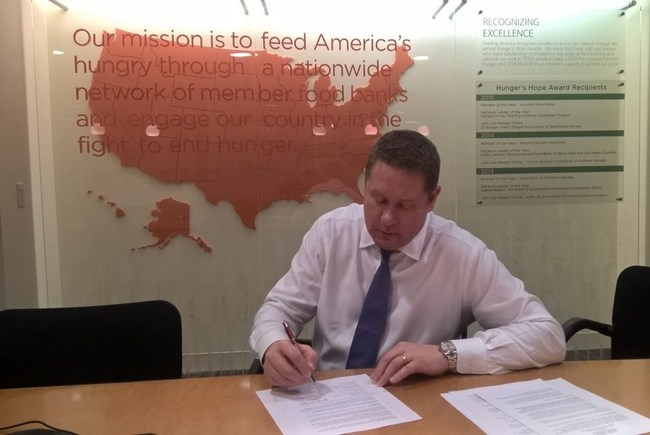 Jay Koster, JLL Group Head, Americas Investor Services, signs an agreement with Feeding America.