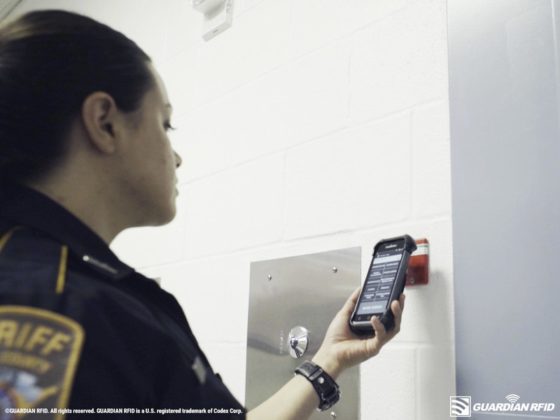 Corrections deputy scanning a GUARDIAN RFID Hard Tag during a cell check.
