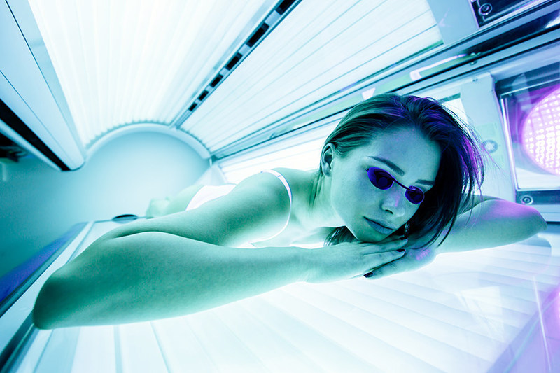 Image of girl in sunbed using proper eyewear (CNW Group/Joint Canadian Tanning Association)