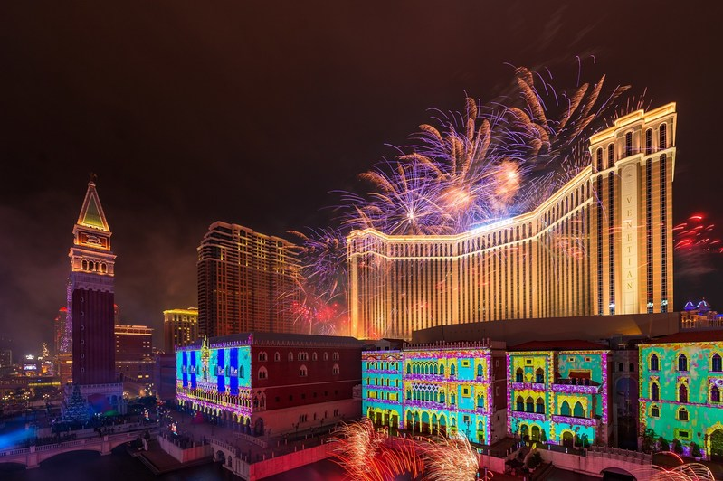 The Venetian Macao's façade is illuminated by 3-D mapping while the sky above is lit up by a pyrotechnic display Monday night at the integrated resort's 10th anniversary celebration.