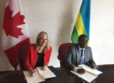La ministre McKenna et le ministre de l'environnement du Rwanda, Vincent Biruta, signent un protocole d'entente de coopération environnementale devant les drapeaux du Canada et du Rwanda. (Groupe CNW/Environnement et Changement climatique Canada)