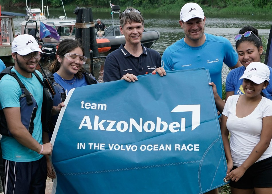Bill Collins, Group Controller for AkzoNobel's Paints & Coatings business (left) and Simeon Tienpont, Skipper of team AkzoNobel, present kids from Rocking the Boat with one of three sails AkzoNobel donated to the non-profit during a visit to Rocking the Boat in July 2017.
