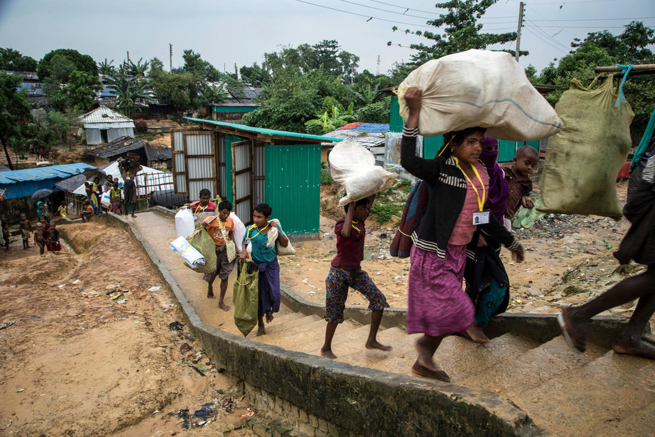 Rohingya refugees carry their personal effects, as they make their way through the winding and complex alleys of Kutupalong refugee camp, in Cox's Bazaar, Bangladesh, Friday 20 October 2017. © UNICEF/UN0140916/LeMoyne (CNW Group/UNICEF Canada)