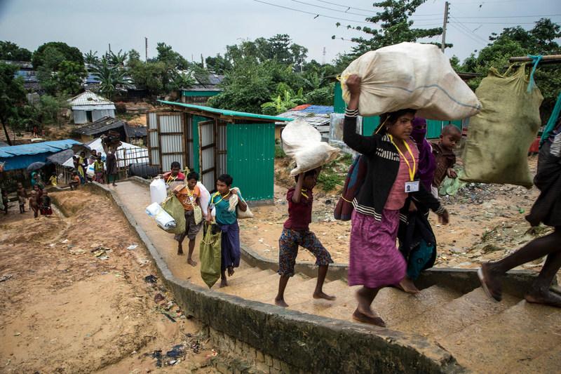 Des réfugiés rohingyas transportent leurs effets personnels et tentent de se frayer un passage dans les allées sinueuses du camps de Kutupalong, à Cox's Bazar, au Bangladesh (20 octobre 2017). © UNICEF/UN0140916/LeMoyne (Groupe CNW/UNICEF Canada)