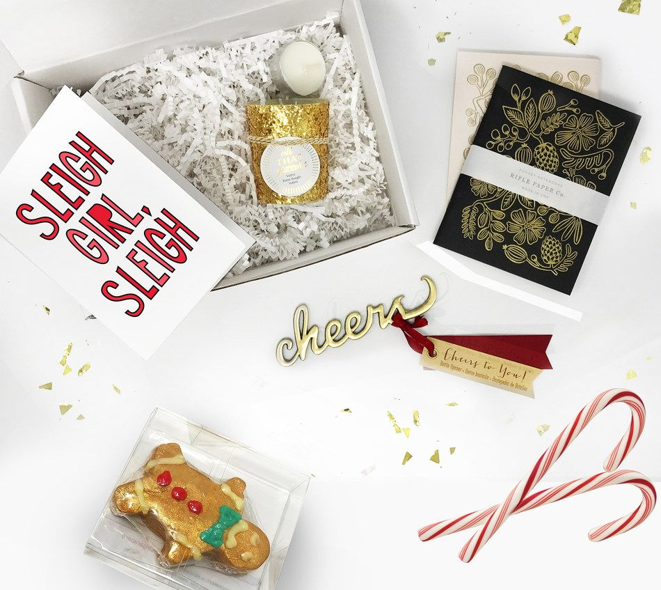 Holiday Happy Box filled with glitter candle, pocket notebooks, 'cheers' bottle opener, gingerbread man organic bath bomb, candy canes, and a card, all topped with gold glitter!